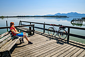 Woman cycling sits on jetty and looks at Chiemsee, Hochgern in the background, Chiemsee Cycle Path, Chiemgau, Upper Bavaria, Bavaria, Germany