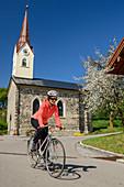 Woman cycling in front of church, Benediktradweg, Chiemgau, Upper Bavaria, Bavaria, Germany