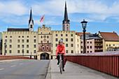 Woman cycling in front of Innbrücke and city gate of Wasserburg, Wasserburg, Benediktradweg, Upper Bavaria, Bavaria, Germany