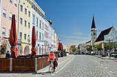 Frau beim Radfahren fährt über Stadtplatz von Mühldorf, Mühldorf, Benediktradweg, Oberbayern, Bayern, Deutschland