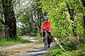Woman rides a bike on dirt road, Inn, Benediktradweg, Upper Bavaria, Bavaria, Germany