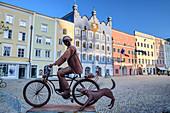 Skulptur mit Radfahrer und Hund am Marktplatz von Burghausen, Burghausen, Benediktradweg, Oberbayern, Bayern, Deutschland