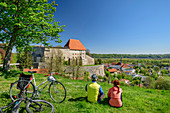 Woman and man cycling while taking a break in front of Burg Tittmoning, Tittmoning, Benediktradweg, Upper Bavaria, Bavaria, Germany
