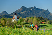 Woman and man cycling, Grainbach and Heuberg in the background, Samerberg, Chiemgau, Chiemgau Alps, Upper Bavaria, Bavaria, Germany