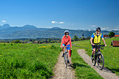 Woman and man cycling, village and Mangfall mountains in the background, Bad Aibling, Upper Bavaria, Bavaria, Germany