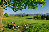 Woman and man cycling while sitting on bench and taking a break, Wilparting Church and Mangfall Mountains in the background, Irschenberg, Upper Bavaria, Bavaria, Germany