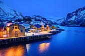 Beleuchtete Fischerhäuser im Hafen von Nusfjord, Nusfjord, Lofoten, Nordland, Norwegen
