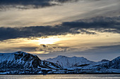 Bad weather clouds over coast and snowy mountains, Napp, Lofoten, Nordland, Norway