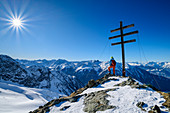 Woman on ski tour stands at the cross of the Wetterkreuzkogel, Ötztal Alps in the background, Wetterkreuzkogel, Stubai Alps, Tyrol, Austria