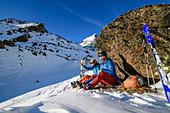 Frau und Mann auf Skitour machen bei großem Felsblock Pause, Hennesiglkopf, Langtauferer Tal, Ötztaler Alpen, Südtirol, Italien