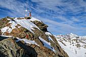Frau auf Skitour steht am felsigen Gipfel des Plereskopf, Plereskopf, Matscher Tal, Ötztaler Alpen, Südtirol, Italien