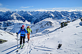 Two women on ski tour ascend to Pangert, Zillertal Alps in the background, Pangert, Tux Alps, Tyrol, Austria