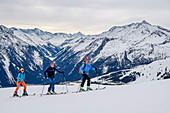Three people on ski tours ascend to the Ronachgeier, Hohe Tauern in the background, Ronachgeier, Kitzbüheler Alpen, Salzburg, Austria