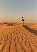 Traveler in the desert dunes off Dubai, UAE