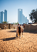 Local saddles a horse at the Heritage Village in Abu Dhabi, UAE