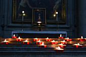 Burning candles in the Basilica Santa Croce in Florence, Italy