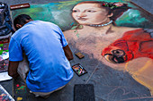 An artist paints the streets of Florence, Italy