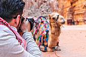 Tourist photographs a camel in Petra, Jordan