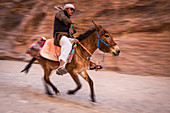 Bedouin rides his donkey through the ancient streets of Petra, Jordan