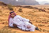 A Bedouin lies in the desert in Wadi Rum, Jordan