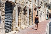 Tourist walks through the streets of Marsaxlokk, Malta