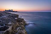 Frau sitzt auf den Steinen außerhalb der Stadtmauern von Valletta und genießt den Sonnenuntergang