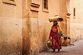 Woman carries various things through the streets of the medina in Marrakech, Morocco