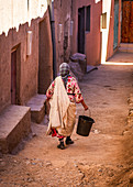 Local people carry a bucket through the streets of Tinghir, Morocco