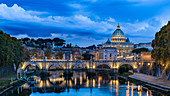 View of the illuminated St. Peter's Basilica and the Angel Bridge shortly after sunset, Rome, Italy