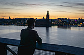 Tourist looking at the sunset over Stockholm, Sweden
