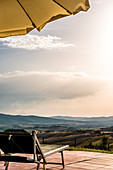 Sunbed and umbrella by a pool, Buonconvento, Tuscany, Italy