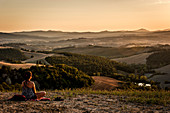 Young woman meditating in the evening light, Buonconvento, Tuscany, Italy