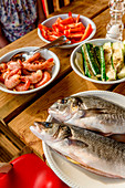 Fresh fish and vegetables on a wooden table