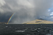A rainbow forms between thick clouds drifting over low mountains, Chilean fjords, Magallanes y de la Antartica Chilena, Patagonia, Chile, South America
