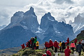 "Tourists vie for the best place to photograph the rugged, iconographic ""towers"" of the mountain range, Torres del Paine National Park, the Magallanes and the Antarctic Chilena, Patagonia, Chile, South America"