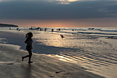 A young woman runs on a wide stretch of beach at low tide in the late afternoon, Manta, Manabi, Ecuador, South America