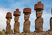A person in the foreground is overshadowed by a group of Moais standing on a ceremonial stone or Ahu from 1250 to 1500, Rapa Nui, Easter Island, Chile