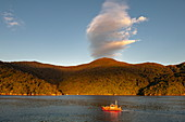 A pilot boat cruises in the late afternoon light against wooded hills and a strange cloud formation, Marlborough Sounds, South Island, New Zealand