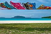 Bunte Stofftücher als Touristen-Souvenirs hängen auf einer Leine am Strand, Insel Espiritu Santo, Vanuatu, Südpazifik