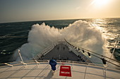 The front of an expedition cruise ship encounters a large wave and sends spray high above the bow at sea in the Caribbean, near Colombia