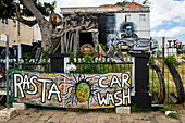 A sign in front of a quirky building advertises 'Rasta Carwash', Willemstad, Curacao, Netherlands Antilles, Caribbean