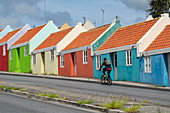 A cyclist passes a row of colorful houses, Pietermaai neighborhood, Willemstad, Curacao, Netherlands Antilles, Caribbean