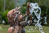 A fountain shows the head and shoulders of a boy blowing a horn from which water emerges, Maracas Bay, Trinidad, Trinidad and Tobago, Caribbean