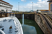 An expedition cruise ship in the Panama Canal is preparing to leave the Miraflores Lock with the grandstand on the right, near Panama City, Panama, Central America