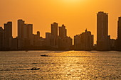 Silhouette of modern skyline with pleasure boats passing by at sunset, Cartagena, Bolivar, Colombia, South America