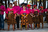A group of Guna (formerly Kuna) natives in bright, traditional costumes prepares for a folklore dance, Isla Aroma, San Blas Islands, Panama, Caribbean