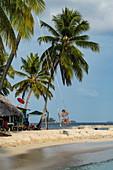 Eine Frau schaukelt am Strand auf einer Schaukel, die an eine Palme gebunden ist, Isla Aroma, San Blas Inseln, Panama, Karibik