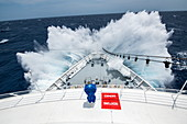 The front of an expedition cruise ship encounters a large wave and sends spray high over the prow, Atlantic Ocean, near Panama, Central America