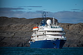 The expedition cruise ship Sea Spirit (Poseidon Expeditions) awaits the return of passengers ashore against the backdrop of barren hills, Alkhornet, Isfjord, Spitsbergen, Norway, Europe