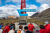 Passengers of the expedition cruise ship Sea Spirit (Poseidon Expeditions) gather around a tour guide at the entrance to the former mining town of Pyramiden, Billefjord, Spitsbergen, Norway, Europe